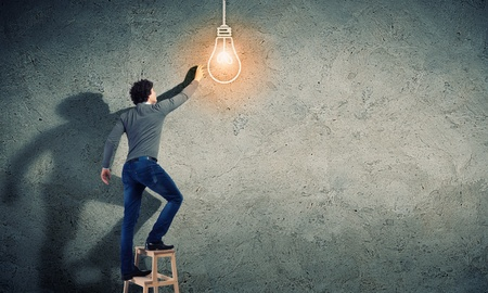 Young man with an electric light bulb against the wall photo