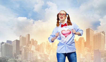 Young woman acting like hero with heart sign on chest photo