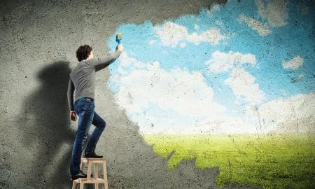 pintor: Joven dibujar un cielo azul y nubes en la pared Foto de archivo