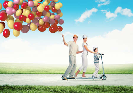Image of happy young family riding on scooter pulling bunch of colorful balloons Stock Photo - 21481238