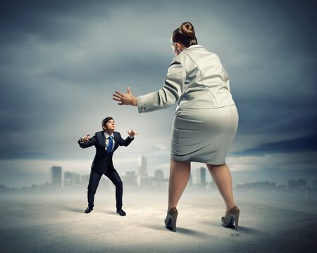 businesspartners: Image of businesspeople arguing and acting as sumo fighters against city background