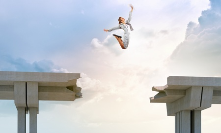 Young woman jumping over a gap in the bridge as a symbol of risk photo