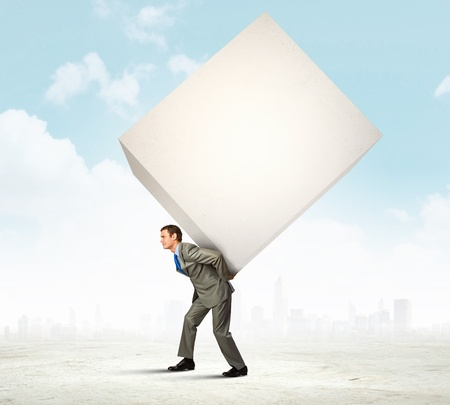 Image of businessman carrying big white cube on his back photo