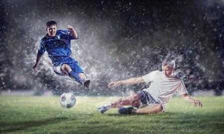 jugadores de futbol: dos jugadores de f?tbol en salto para golpear la pelota en el estadio
