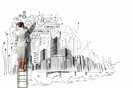 Businesswoman standing on ladder and drawing sketch on wall photo