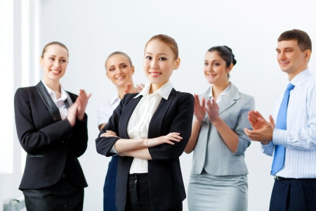 joyfully: Young asian businesswoman smiling with colleagues applauding joyfully at background