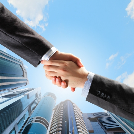 Close up image of hand shake against skyscrapers photo