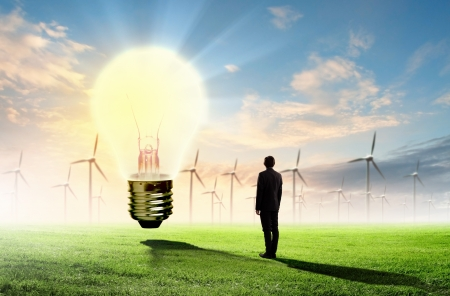 Image of businessman looking at light bulb  Green energy concept