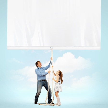 Man and little girl pulling banner  Place for text photo