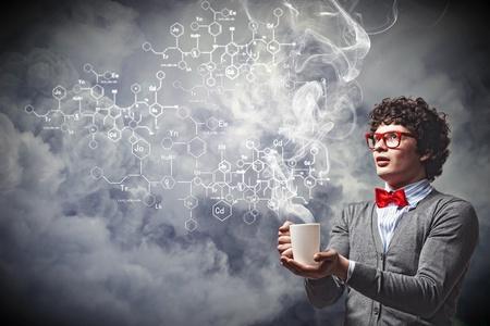 investigador cientifico: Hombre joven con el humo que sale de una taza experimentar
