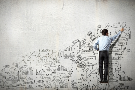 business project: Back view of businessman drawing sketch on wall