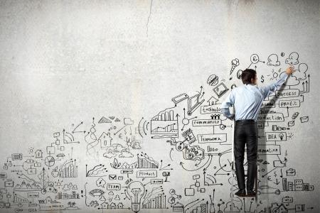 Rückansicht des Geschäftsmann Zeichnung Skizze auf Wand Standard-Bild