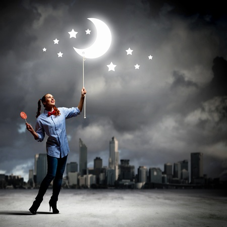 Funny teenager girl with candy against city background photo