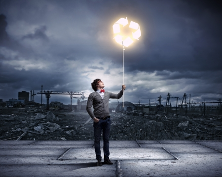Young man with a recycle symbol against a polluted and ruined landscape Stock Photo