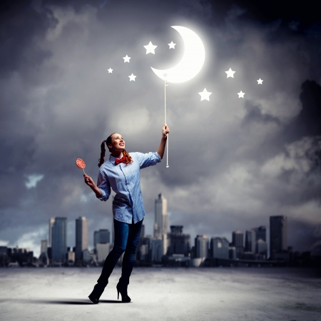 woman night: Funny teenager girl with candy against city background