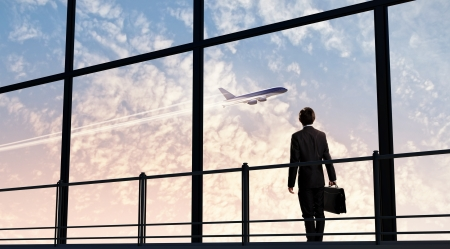 airport terminal: Image of businessman at airport looking at airplane taking off