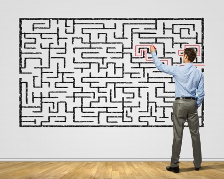 game plan: Back view image of young businessman trying to find way out of maze