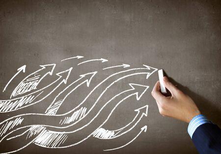 Close up of human hand drawing arrows photo