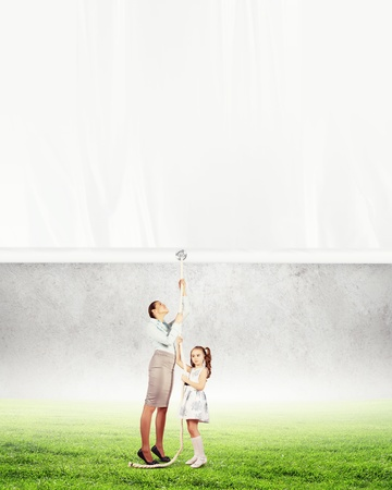 Woman and little girl pulling banner  Place for text photo