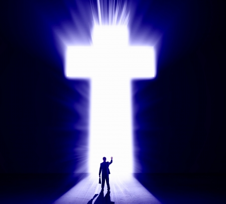 Silhouette of businessman against cross in light Stock Photo - 21579473