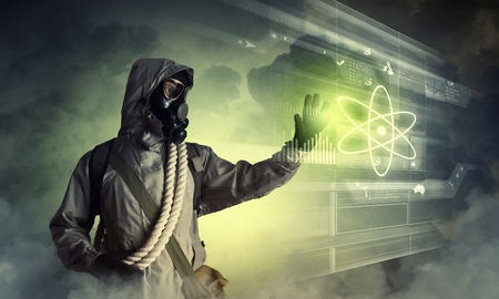 Image of man in gas mask and protective uniform touching atom sign photo