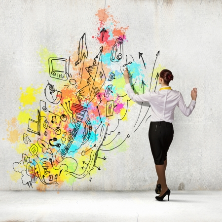 planing: Back view of businesswoman drawing colorful business ideas on wall Stock Photo