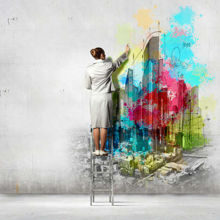 Back view of businesswoman drawing colorful business ideas on wall photo