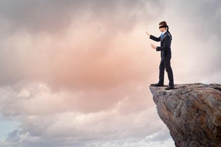 Afbeelding van zakenman in blinddoek staan op de rand van de berg