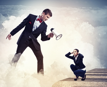 Angry businessman with megaphone shouting at colleague photo