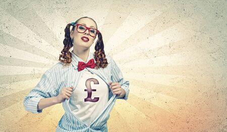 moneymaking: Young woman acting like super hero with pound sign on chest Stock Photo