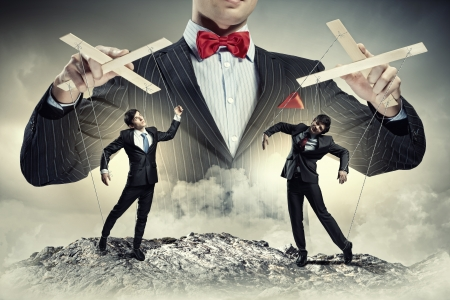 exploitation: Image of young businessman puppeteer  Leadership concept Stock Photo