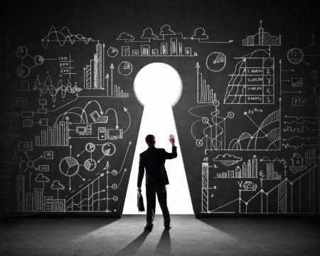 黒い壁に鍵穴と実業家のシルエット