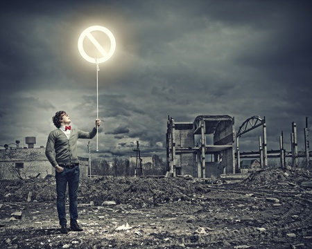 Young man and stop sign against polluted and ruined landscape Stock Photo - 21647525
