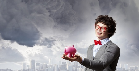 Image of young businessman in red glasses holding moneybox photo