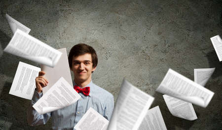 Image of young tired man holding folder with documents photo