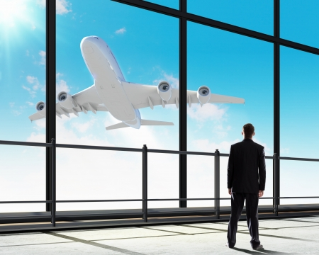 airplane take off: Image of businessman at airport looking at airplane taking off