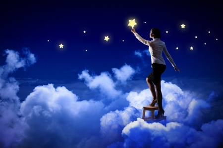 wishes romantic: Image of young woman lighting stars in night sky Stock Photo