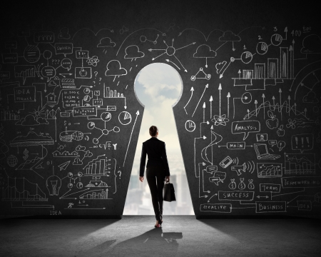 business improvement: Silhouette of businesswoman against black wall with key hole