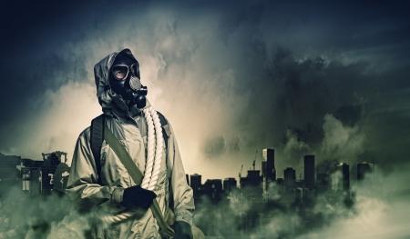 El hombre en la máscara de gas contra el fondo de desastres Concepto de la contaminación