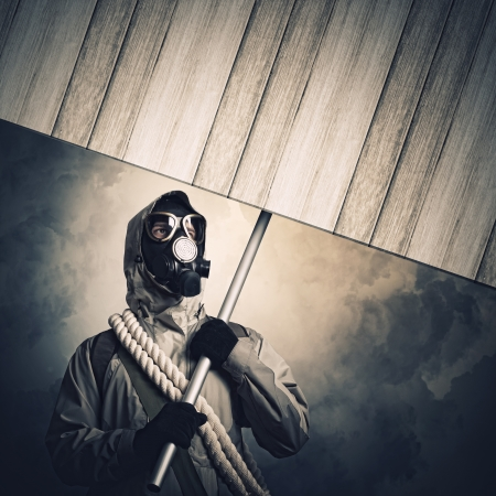 Stalker in gas mask with wooden banner  Disaster concept photo