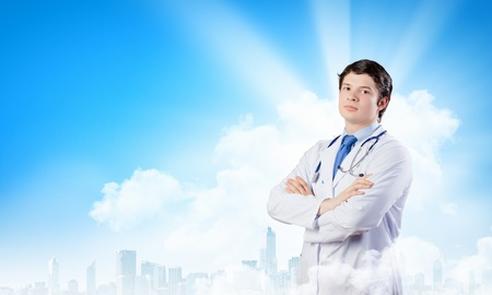 Image of happy confident doctor in uniform against blue background photo