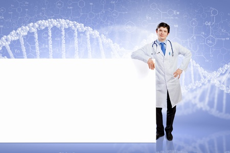 Young male doctor leaning upon blank banner  Place for text photo