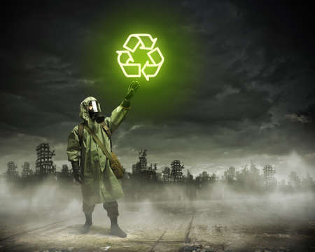 Image of man in gas mask and protective uniform touching recycle sign photo