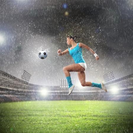 Image of young woman football player hitting ball photo