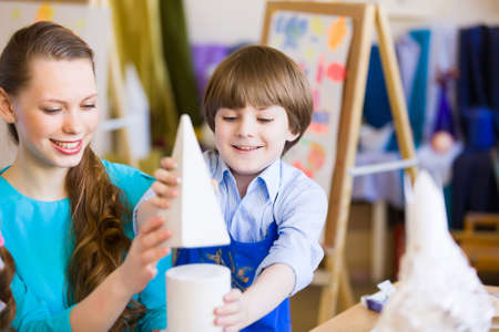 Young teacher and children painting and playing photo