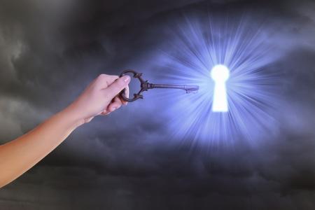 鍵穴にキーを挿入する人間の手のイメージをアップします。