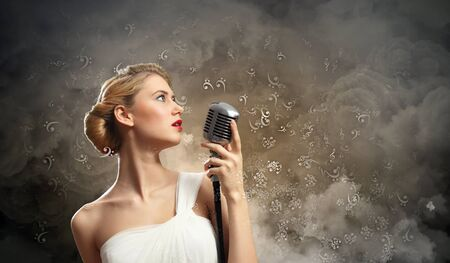 Image of female blonde singer holding microphone against smoke background photo