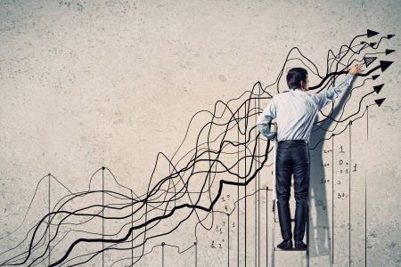growth in economy: Back view image of businessman drawing graphics on wall