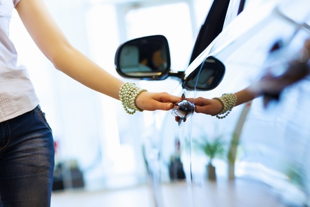 car show: Pretty woman standing near car at car center  Choosing a car