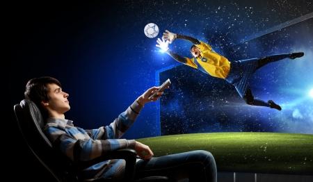 Jonge man kijken naar voetbalwedstrijd op tv Stockfoto